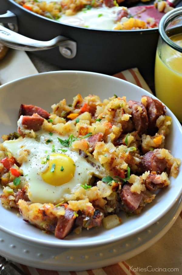 Kielbasa Breakfast Skillet in a bowl with an over-easy egg next to skillet filled with remaining food.