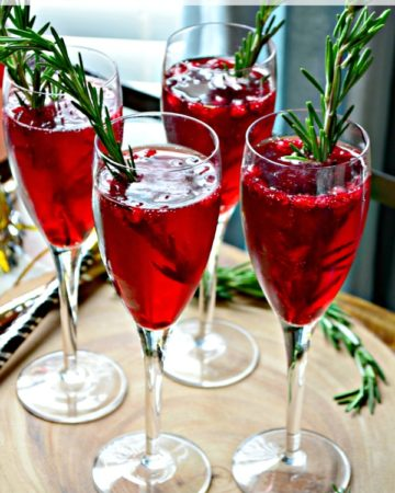 Four Pomegranate Rosemary Sparkling Cocktails in champagne flutes with rosemary in glass.