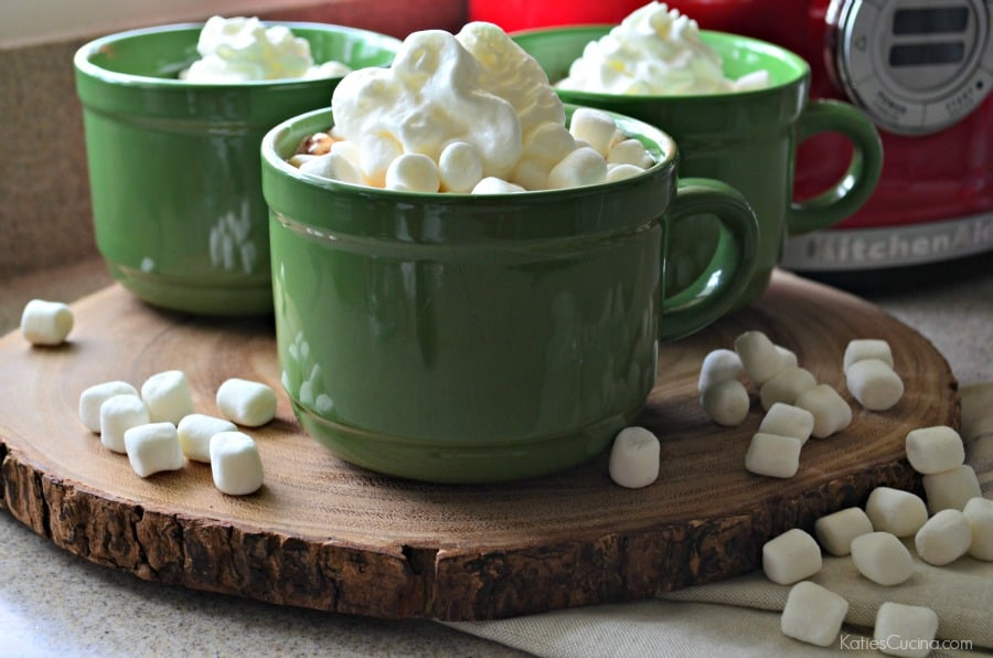 Three green mugs sitting on a slice of wood filled with whipped cream and marshmallows on the counter.