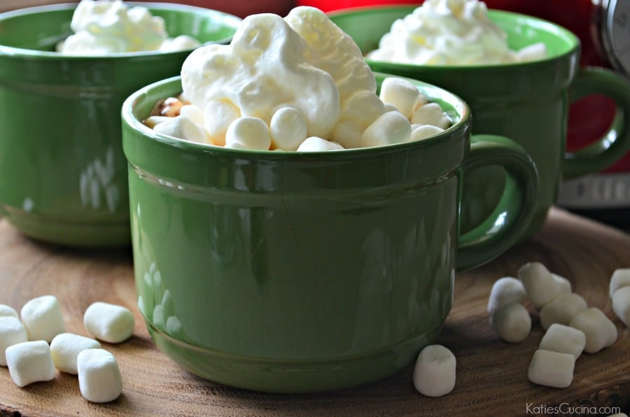 Close up of three large green mugs on a wood slice with mini marshmallows on top.