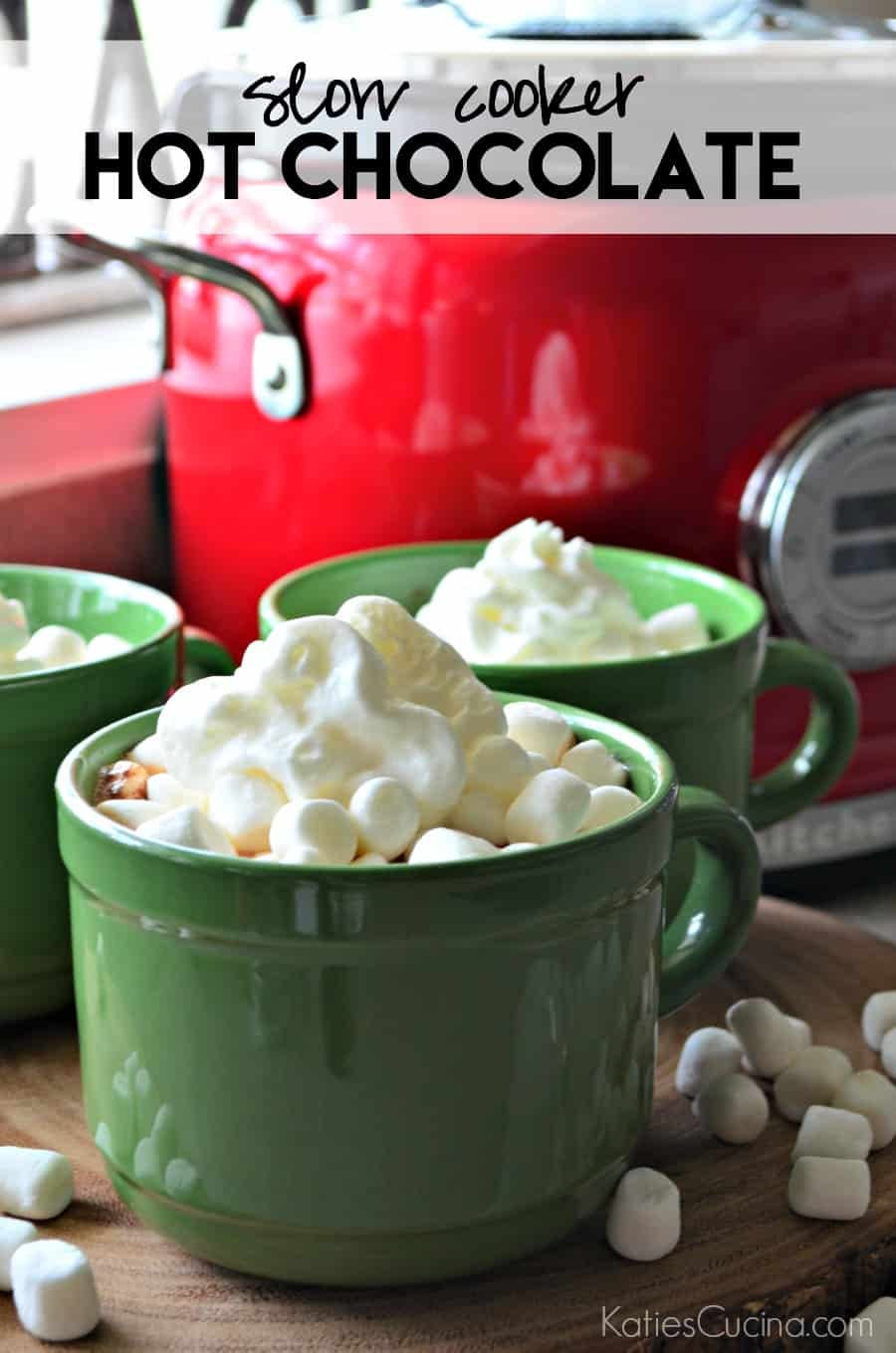 Red slow cooker in background with green mugs filled with whipped cream and text on image.