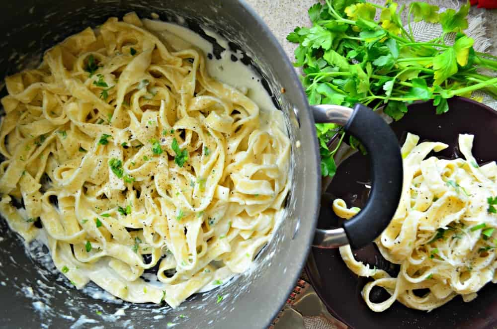 Top view of a big pot of Fettuccine Alfredo topped with fresh parsley and black pepper.