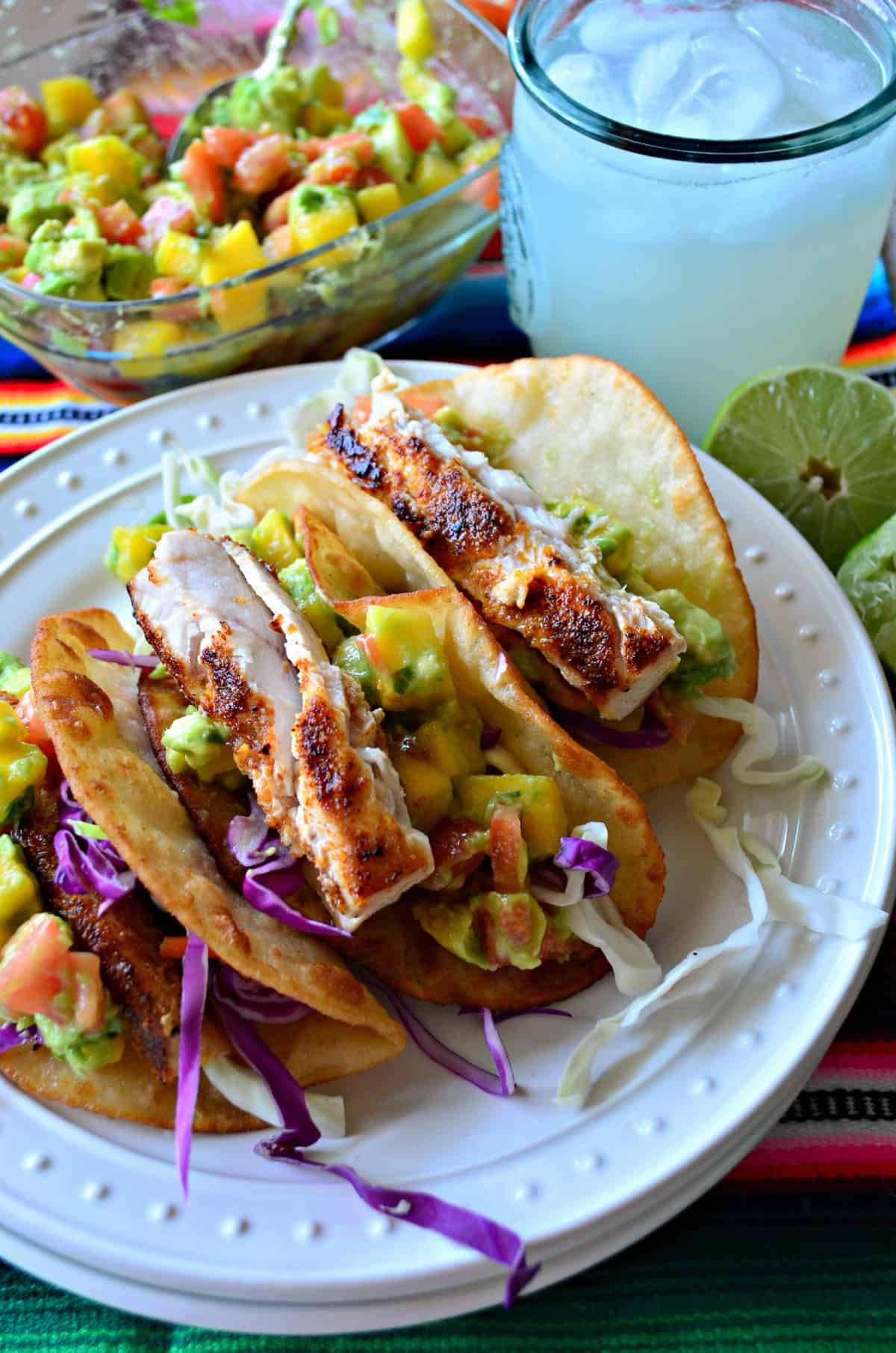 closeup Fish Tacos with Mango Avocado Salsa with a margarita and avocado mango salsa in the background.