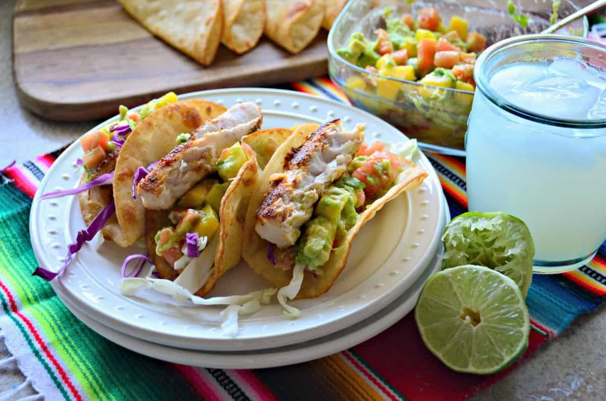 3 plated Mahi Mahi Fish Tacos with Mango Avocado Salsa next to lime and a yellow iced beverage.