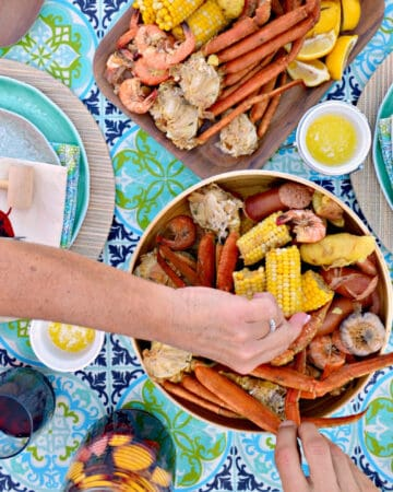 Female and man hand grabbing crab legs and corn in a seafood bowl.