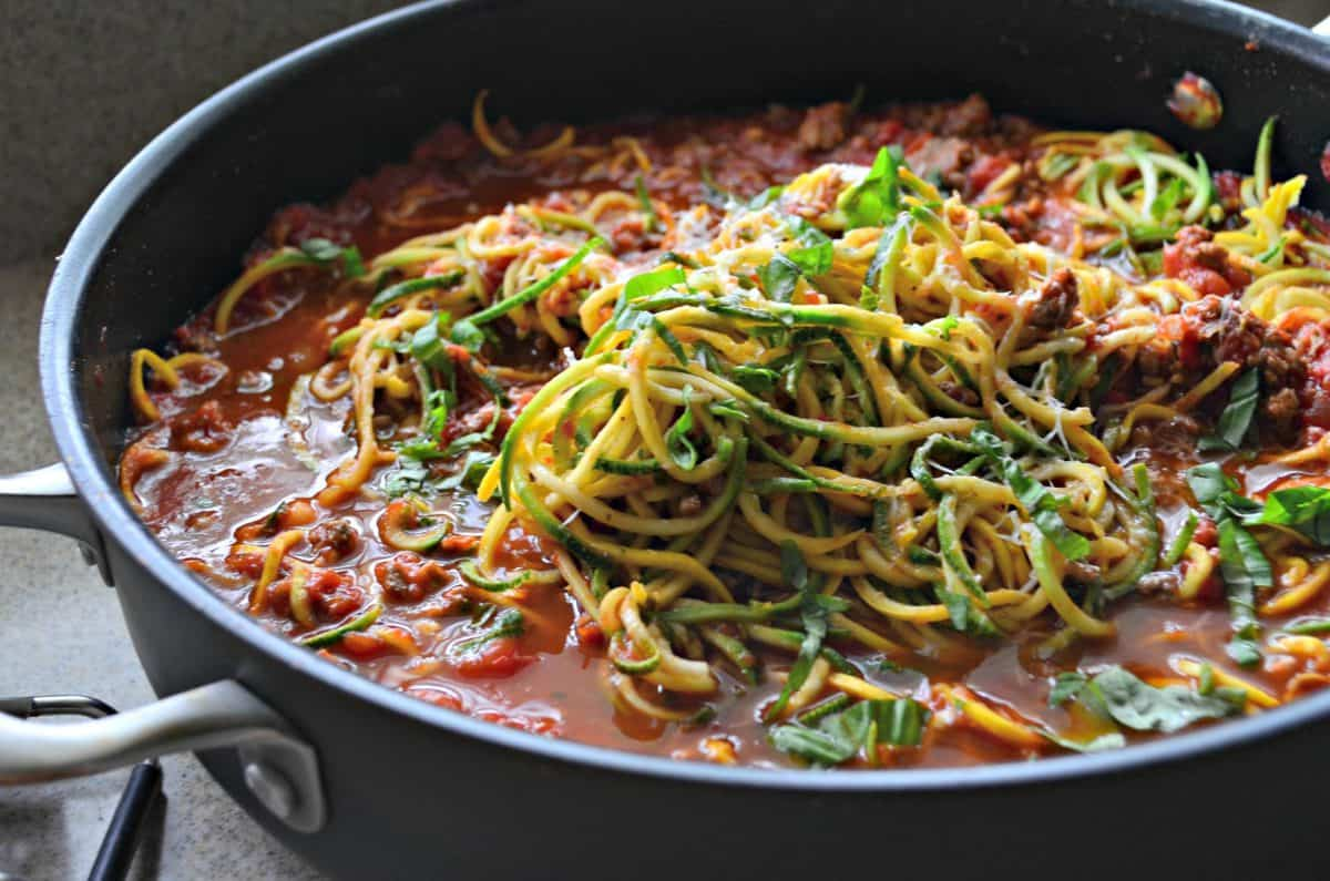 Black skillet filled with meat sauce, zucchini noodles, and cheese.