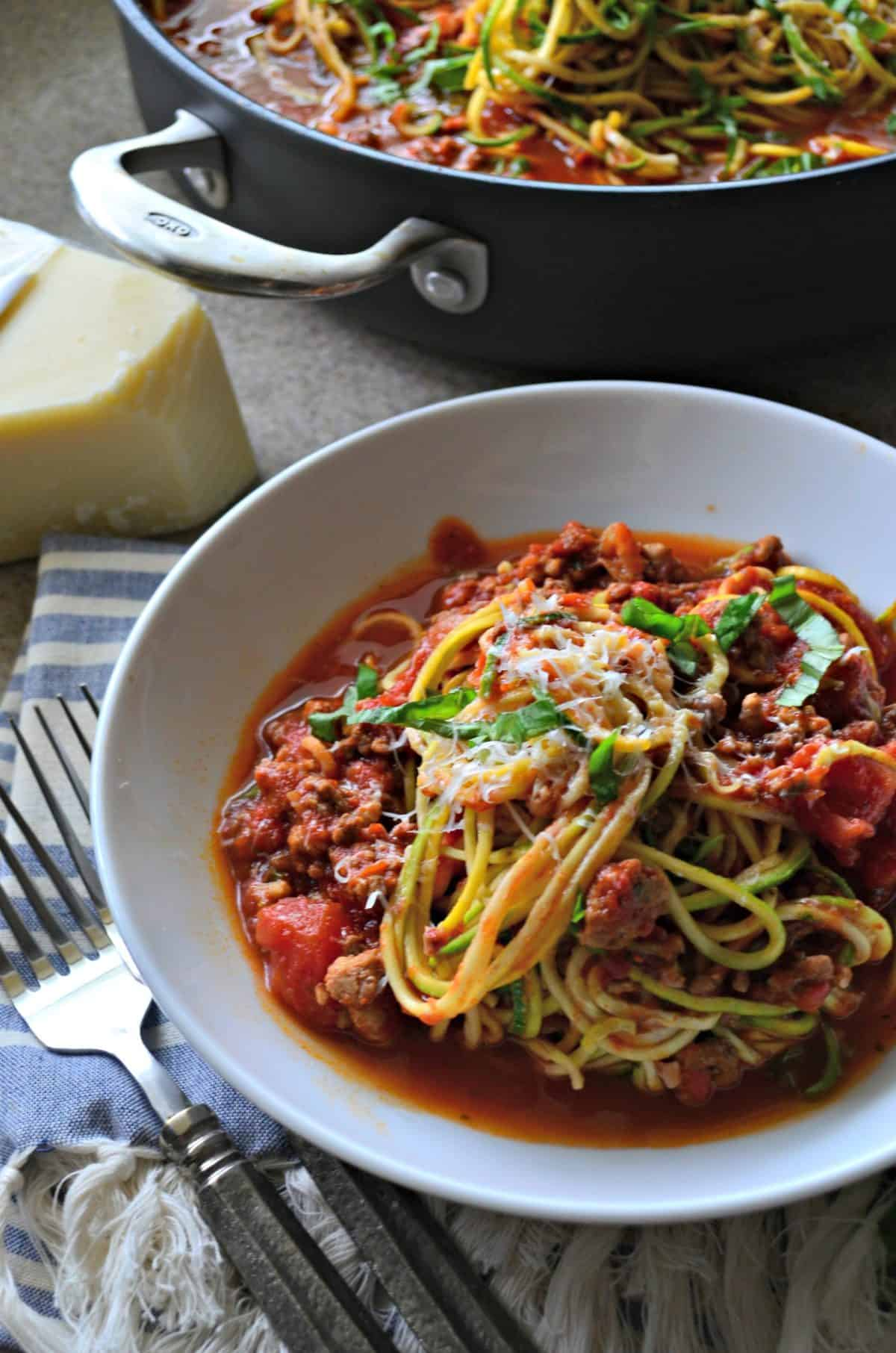 White bowl filled with zucchini noodles and meat sauce with skillet in background.