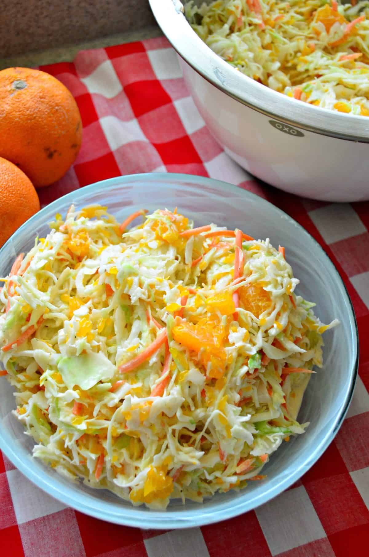 Overhead view of coleslaw with oranges on a red and white checkered cloth.