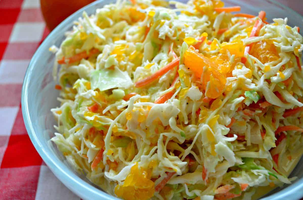 Side view of a blue bowl with coleslaw with oranges in it on a red and white checkered cloth.