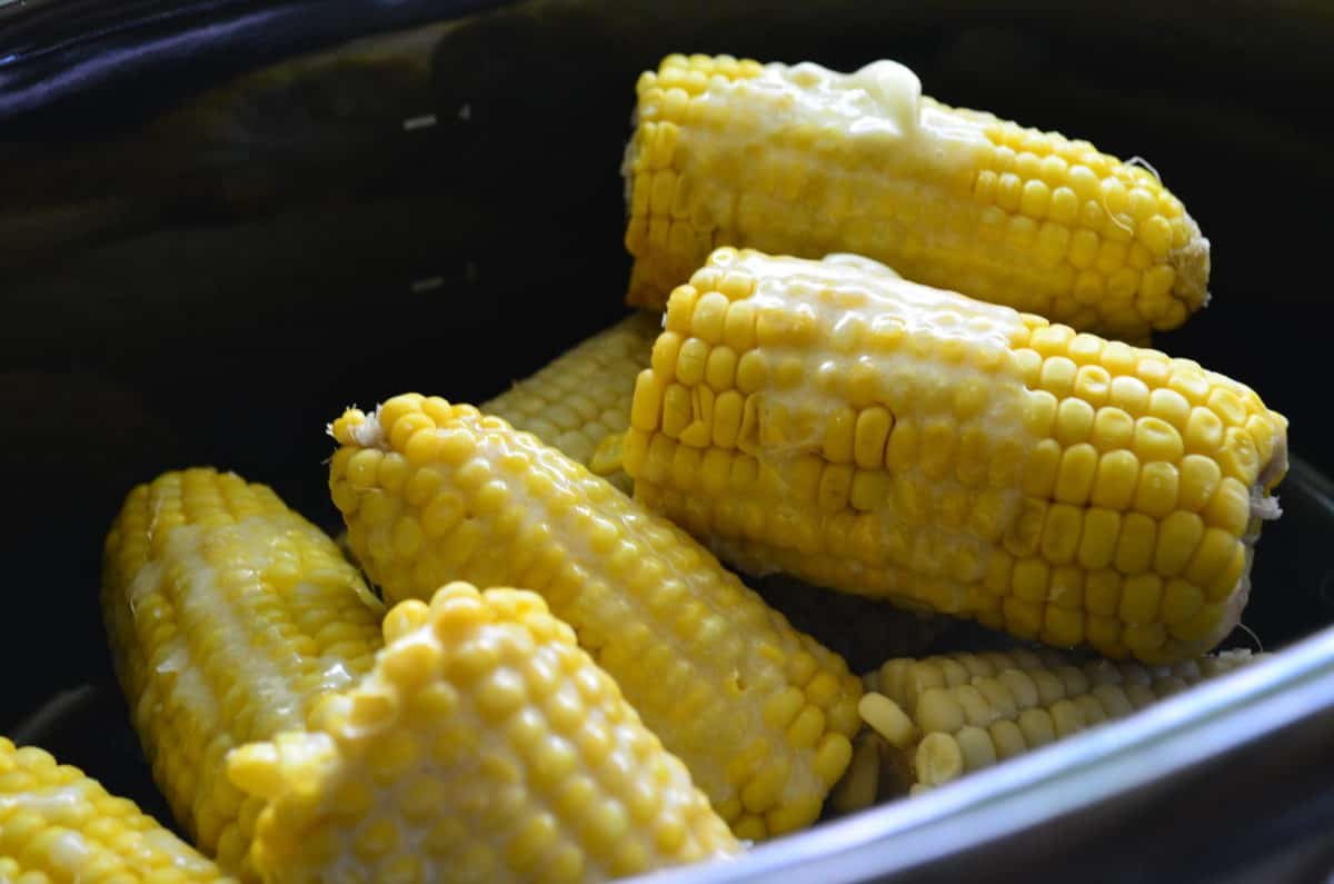 Half ears of cooked corn on the cob drizzled in butter in a black pot.