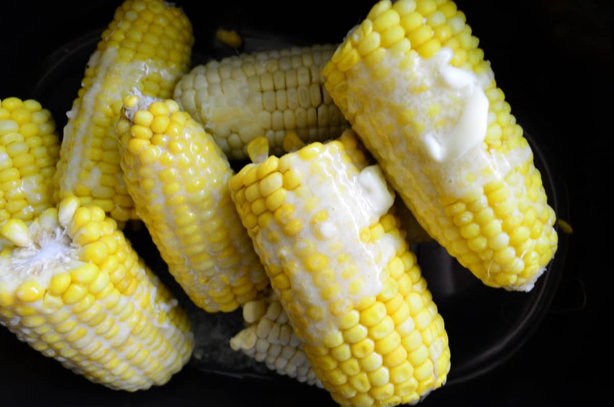 Top view of half pieces of con on the cob with butter on them.