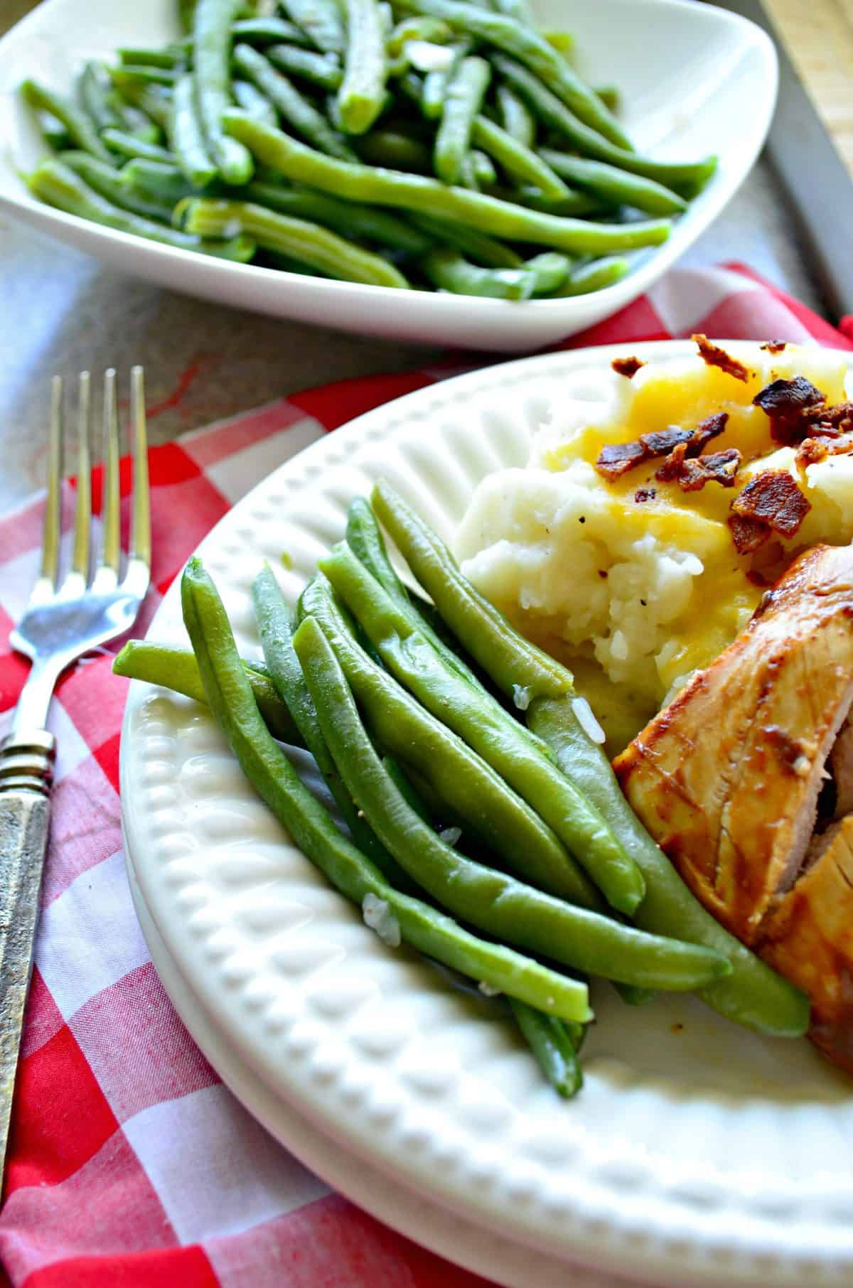 closeup of cooked green beans on white plate with chicken and mashed potatoes next to metal fork.