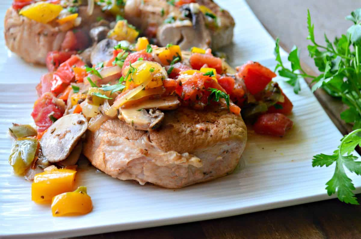 plated pork chops covered in herbs, tomatoes, mushrooms, and parsley on white plate.