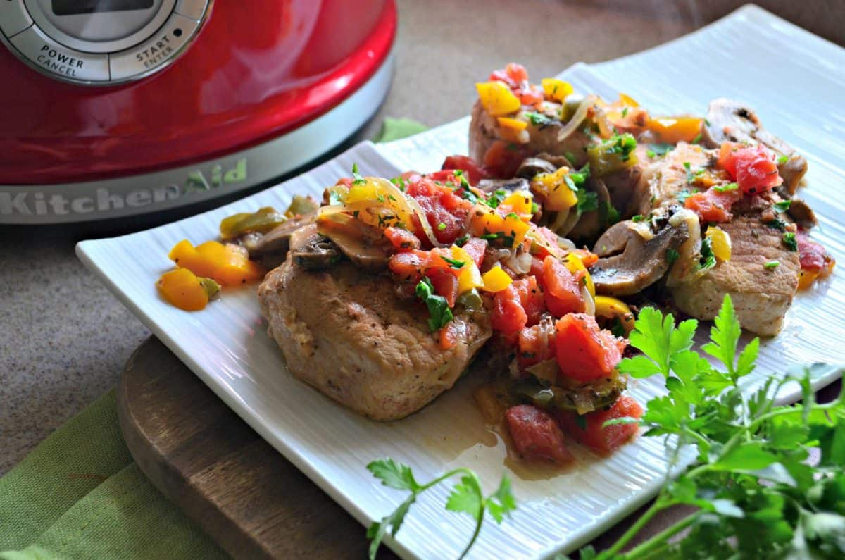top view of pork chops covered in herbs, tomatoes, mushrooms, and parsley on white plate in front of red slow cooker.
