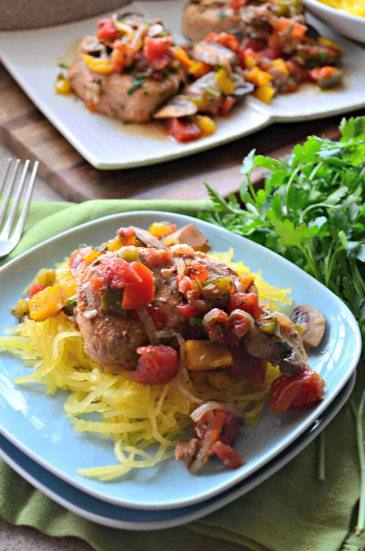 closeup top view of pork chops covered in herbs, tomatoes, mushrooms, over spaghetti squash.
