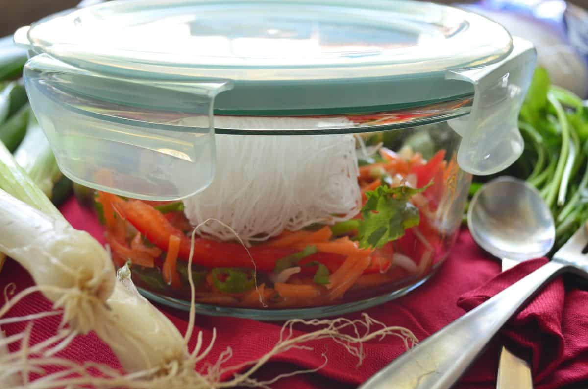 side view of closed glass container filled with uncooked sliced peppers, rice noodles, cilantro, and bean sprouts.