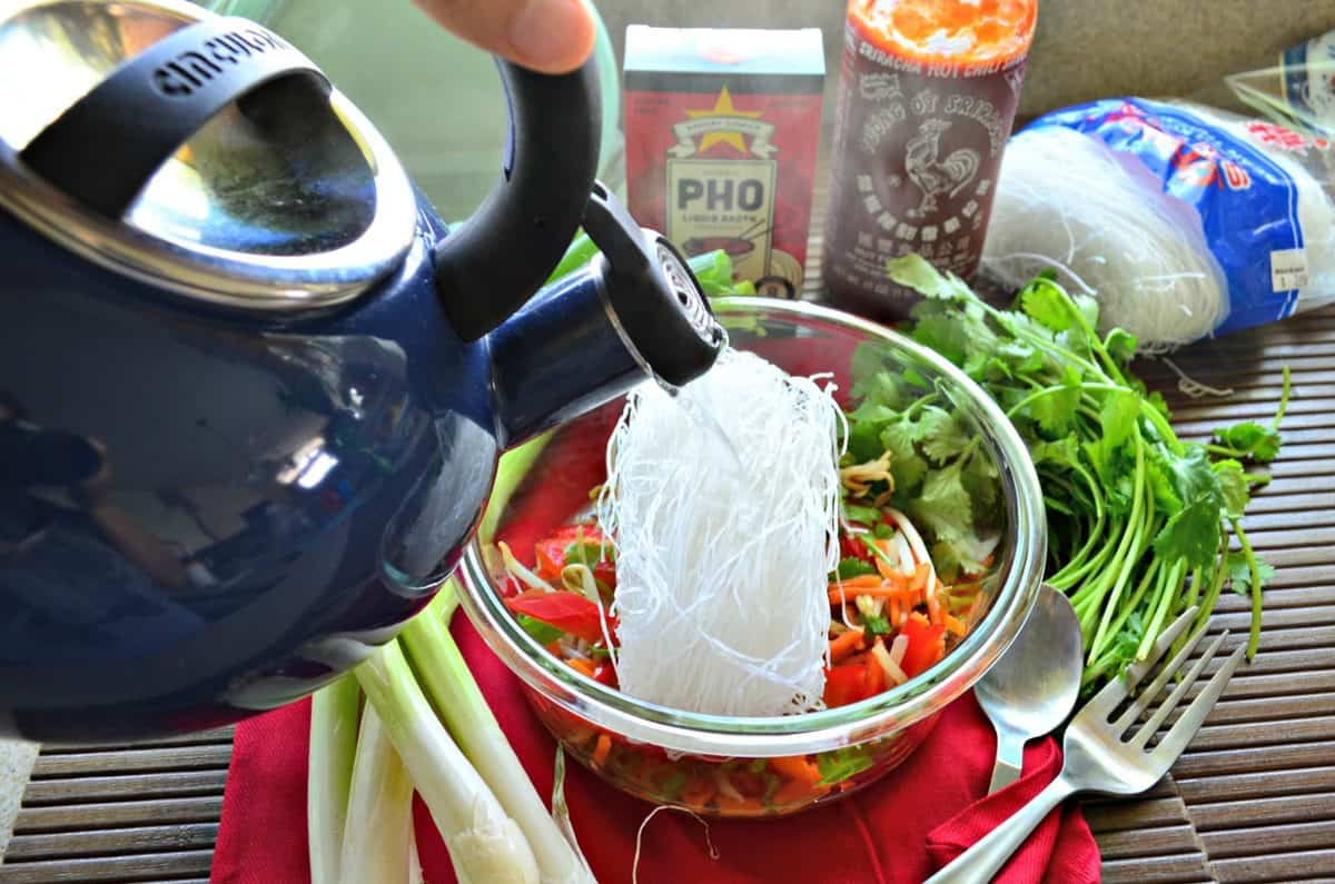 top view of kettle held over glass container filled with uncooked sliced peppers, rice noodles, cilantro, and bean sprouts.