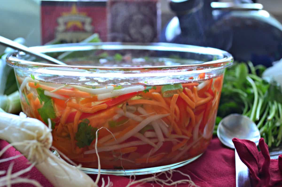 side view glass container filled with sliced peppers, rice noodles, cilantro,  bean sprouts, and broth.