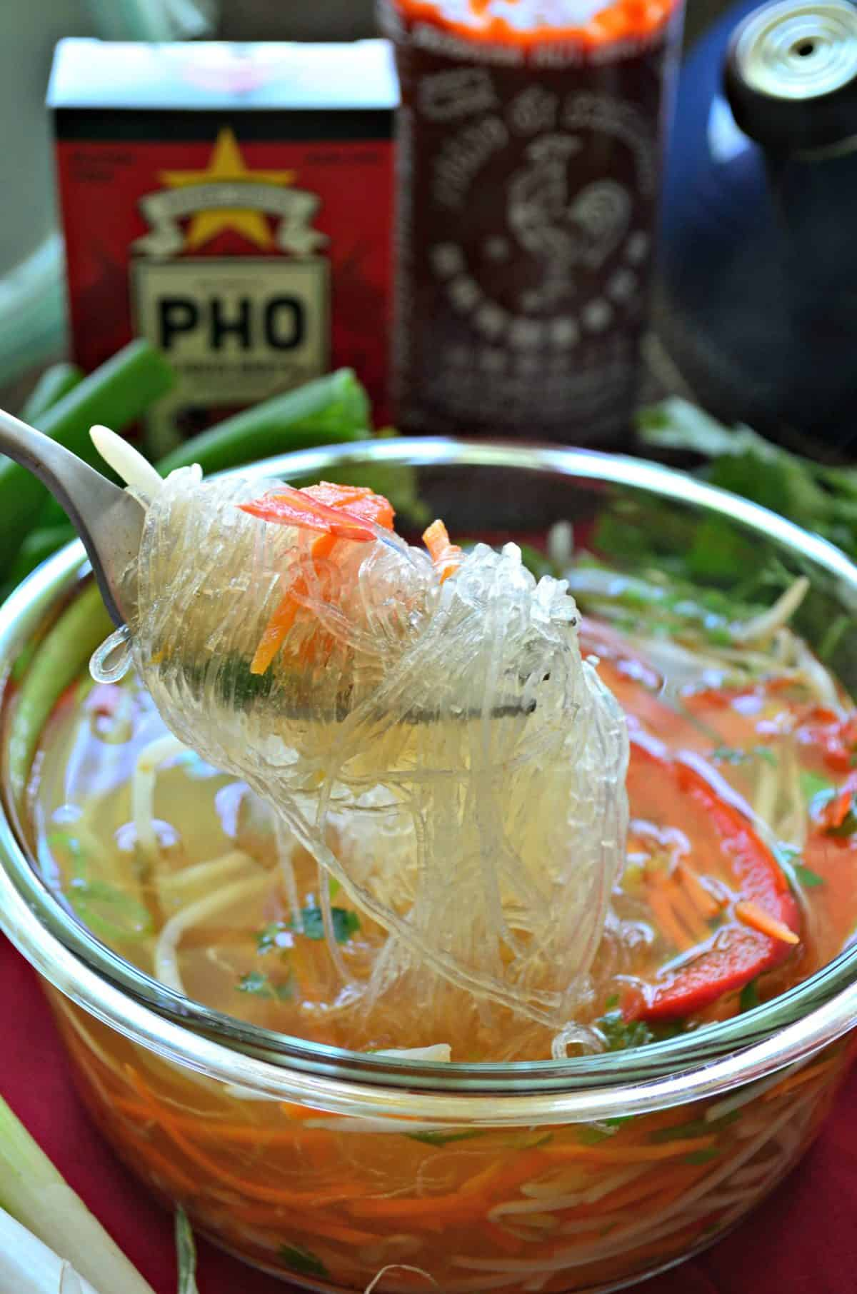 closeup fork full of rice noodles over bowl of pho filled with broth and veggies.