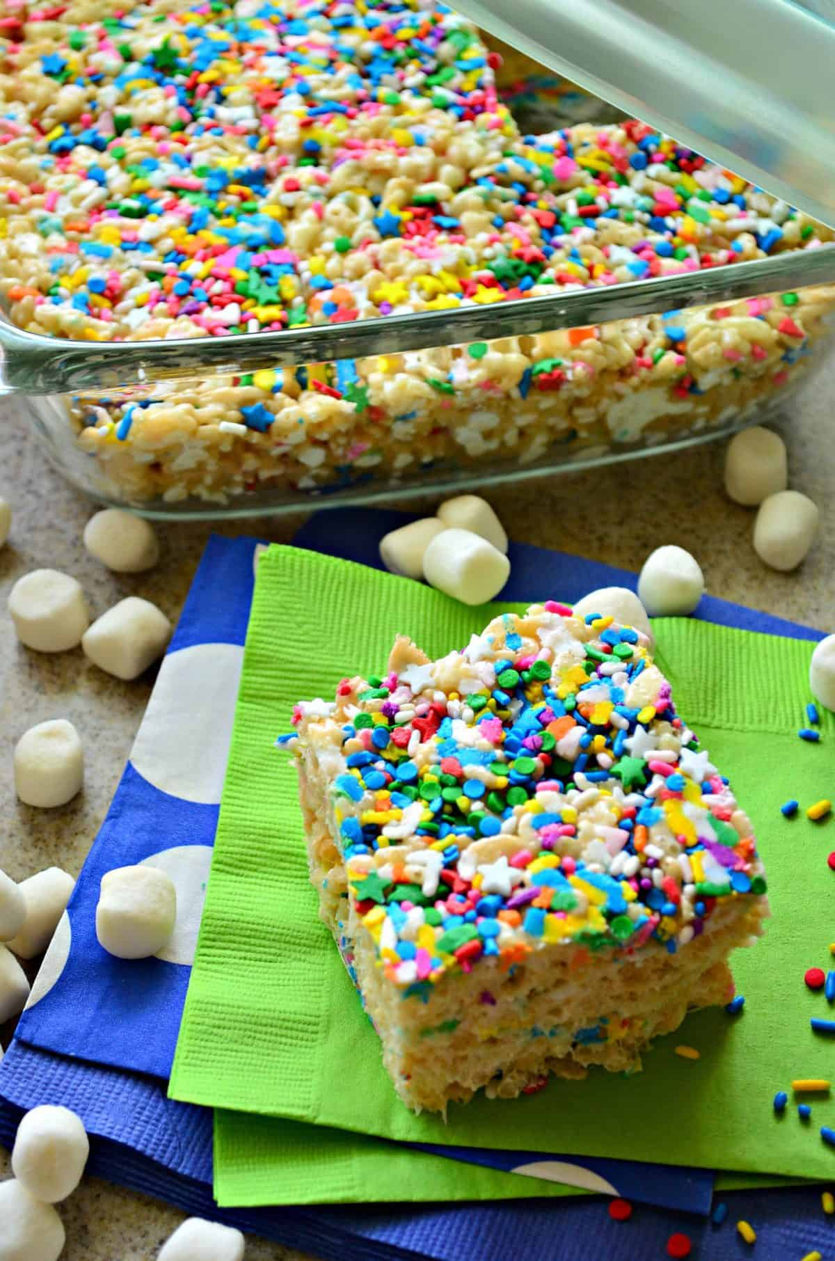 colorful rice crispy square on green napkin in front of glass casserole dish of remaining uncut rice crispy treat.