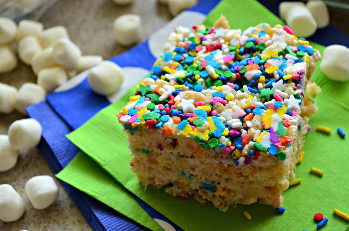 closeup of colorful sprinkle topped rice crispy square on green napkin with mini marshmallows and title text.