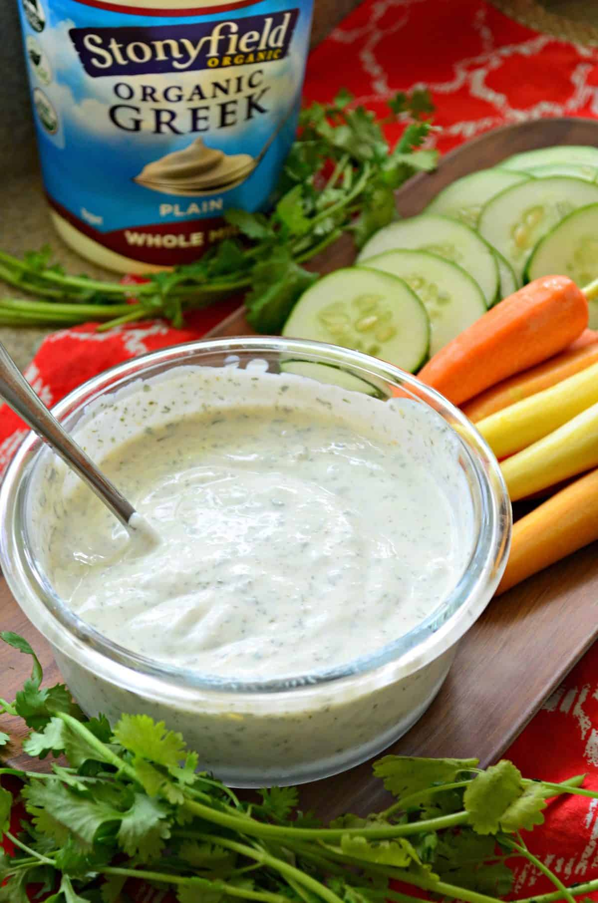 white herbed dip in glass bowl with metal spoon on wooden platter with sliced cucumbers and carrots.