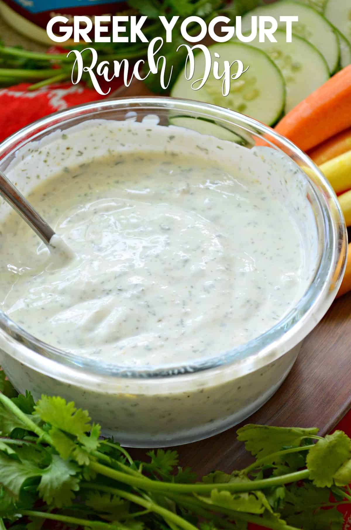 closeup of Greek Yogurt Ranch Dip in glass bowl with metal spoon, veggies in background, and title text.