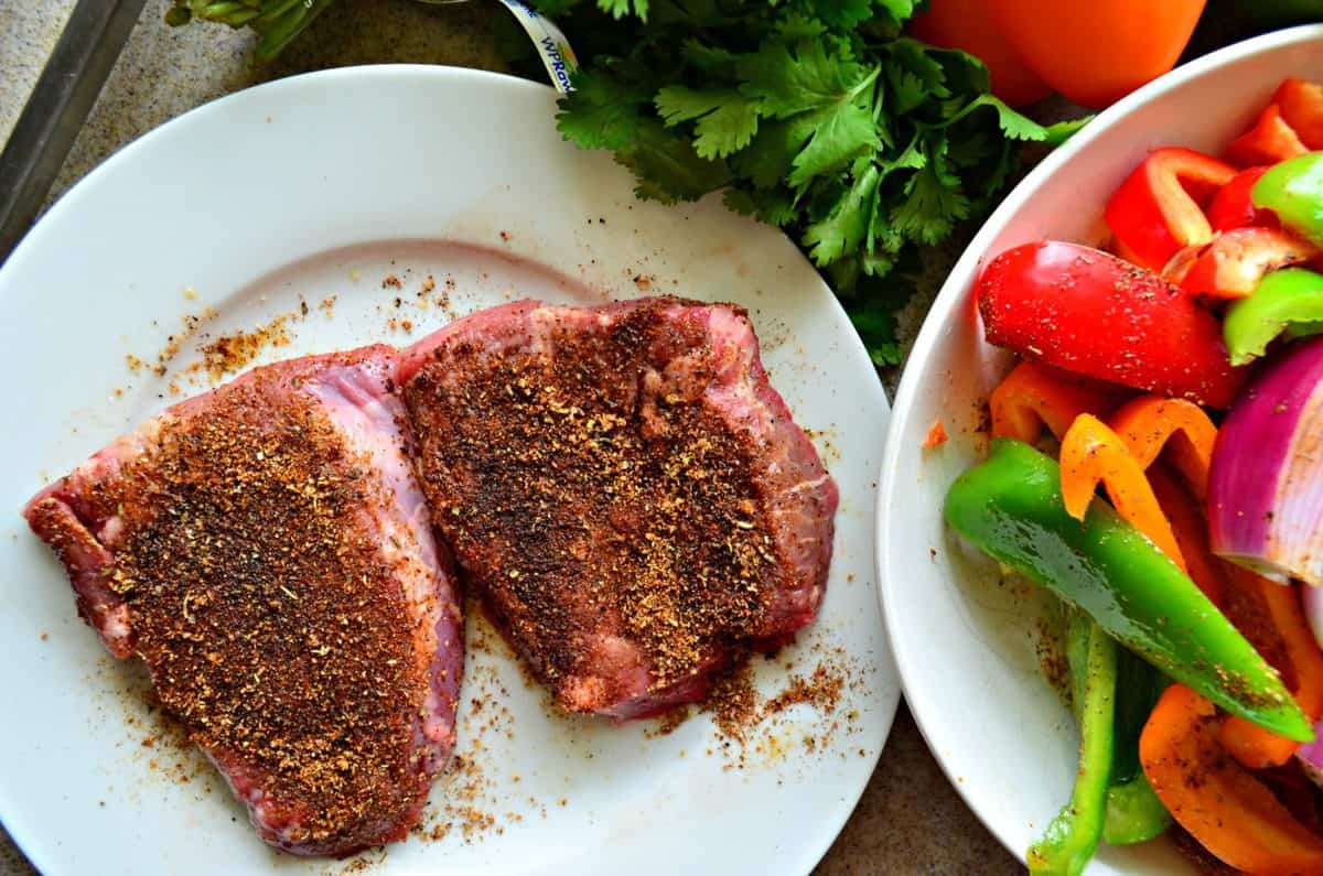 top view of 2 plated slices of uncooked steak dusted with seasonings next to bowl of uncooked veggies.