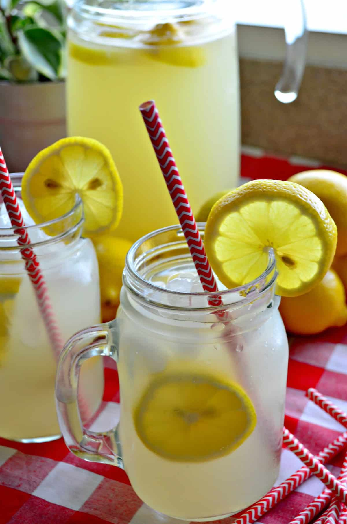 Closeup side view of lemonade in two mason jars with fresh lemon wheels and red straws and pitcher in background.