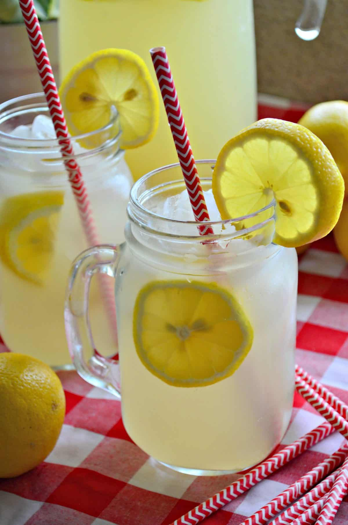 Closeup side view of lemonade in two mason jars with fresh lemon wheels and red straws.