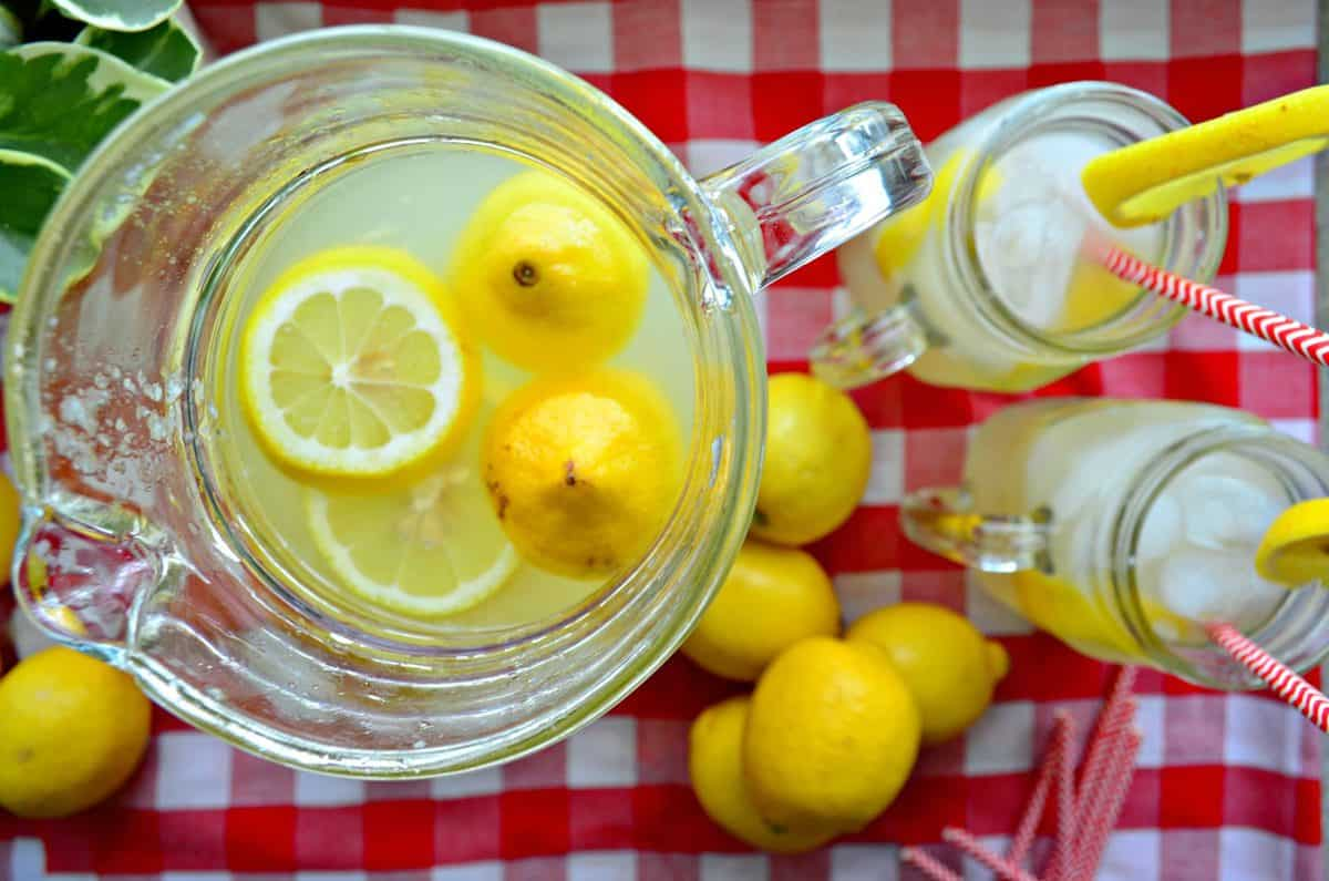 Top view pitcher of lemonade with fresh lemon wheels next to two jars of lemonade on tablecloth.