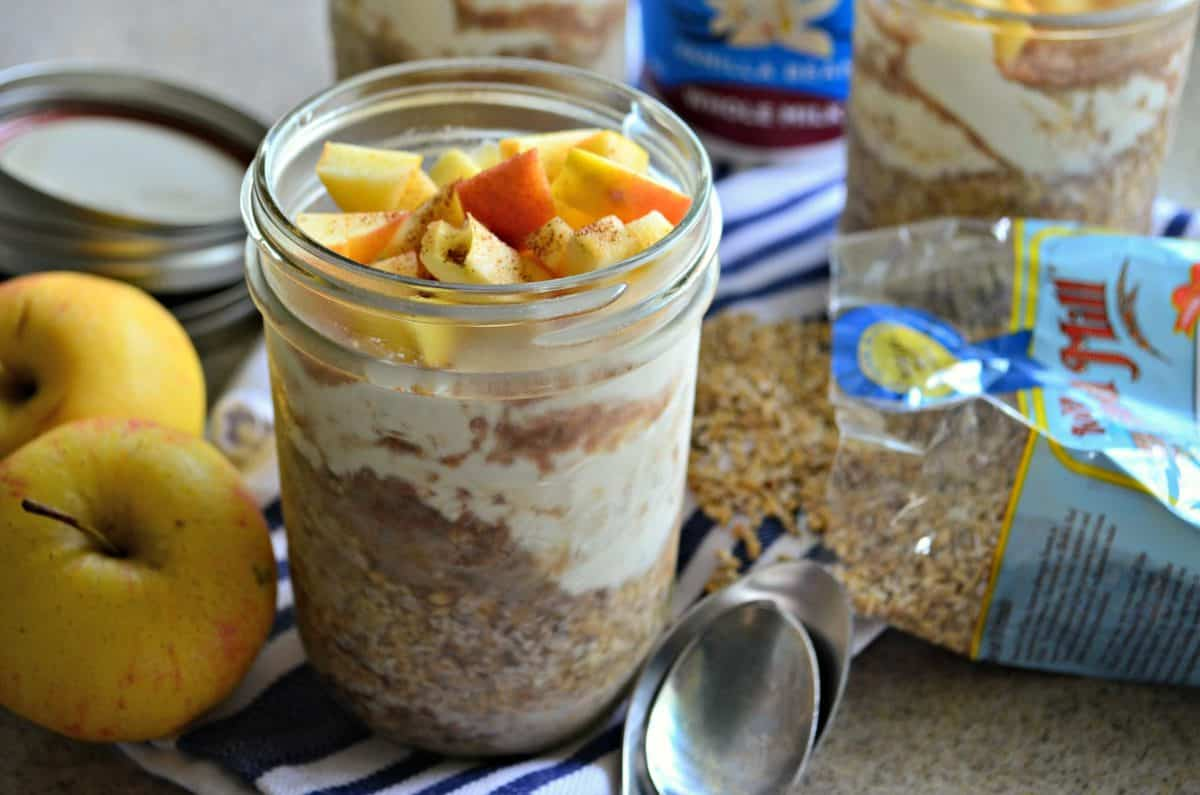 glass filled with yogurt, oats, and topped with apple slices and cinnamon on cloth next to spoon and apples.