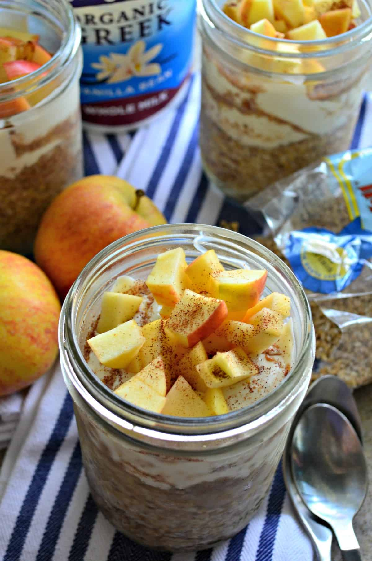 top view of 3 glasses filled with yogurt, oats, and topped with apple slices and cinnamon.