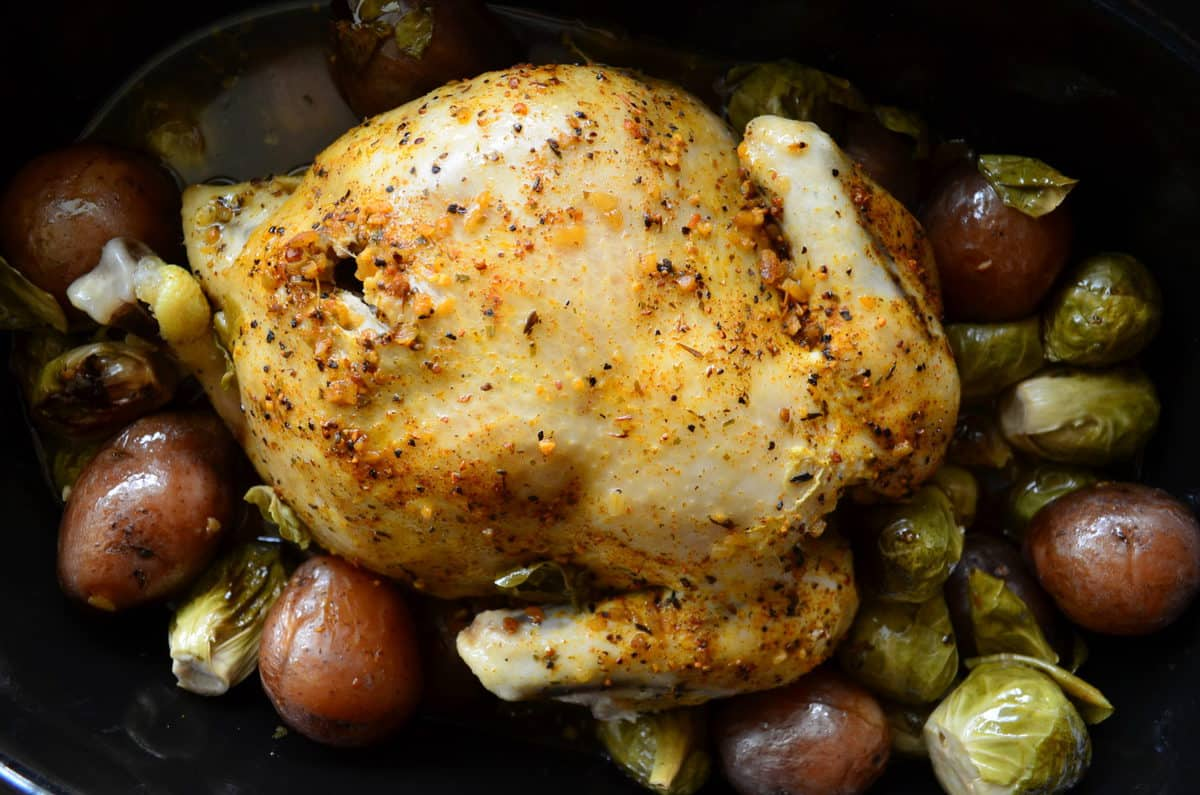 Top view of Golden browned chicken topped with herbs in slow cooker with potatoes and brussels sprouts.