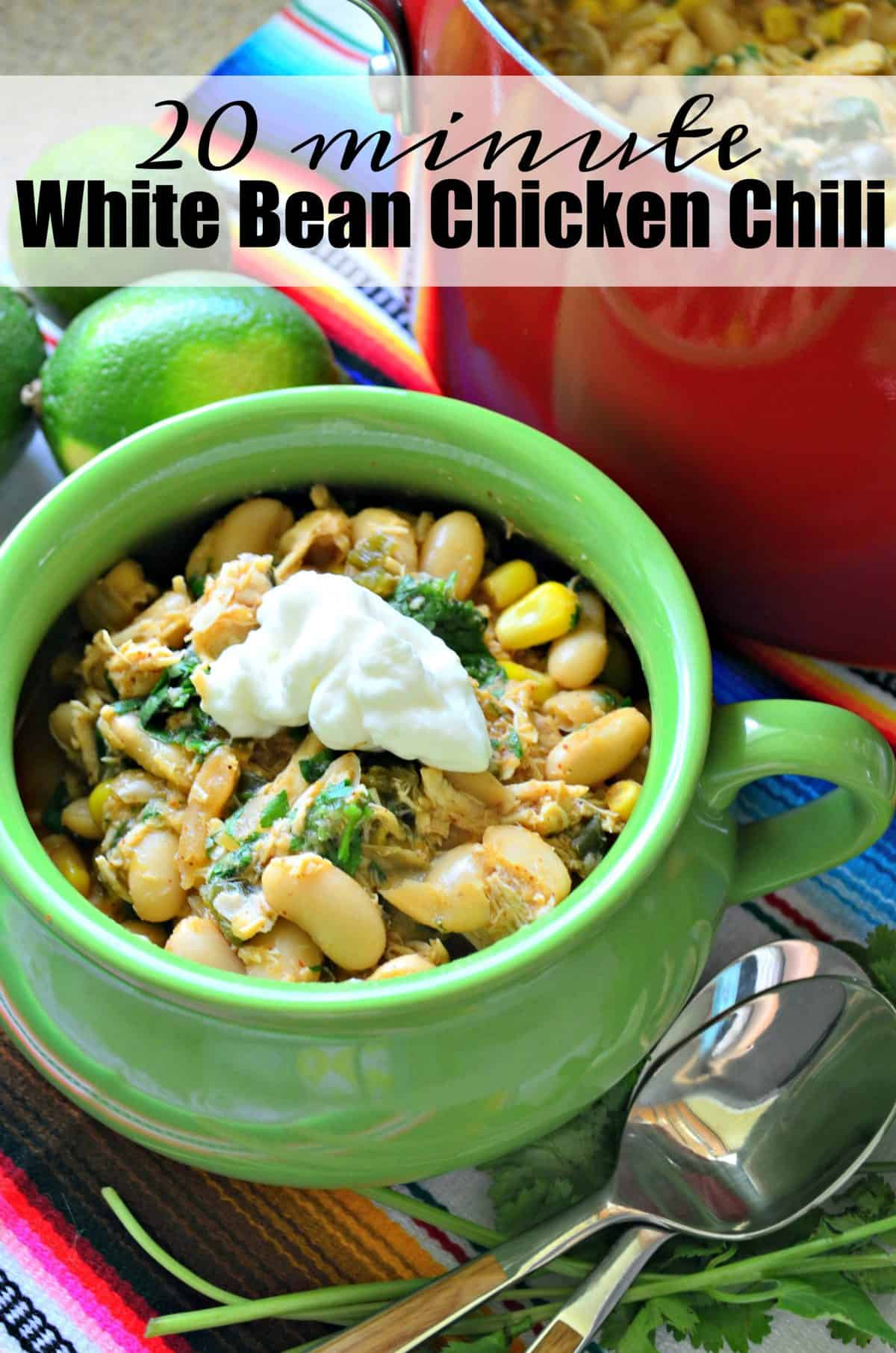 White Bean Chicken Chili topped with green herbs and sour cream in a small green mug next to spoons.