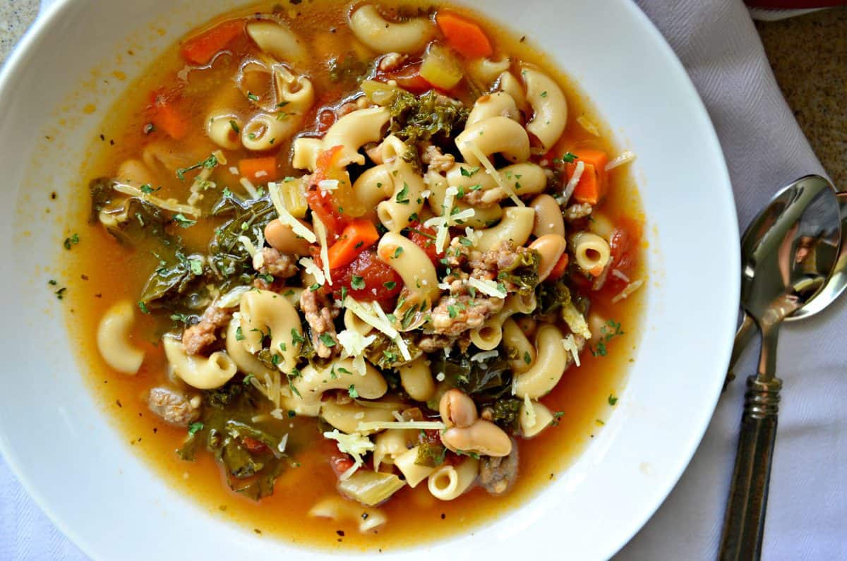 top view of white bowl of soup with macaroni noodles, beans, greens, carrots, and tomatoes next to spoon.