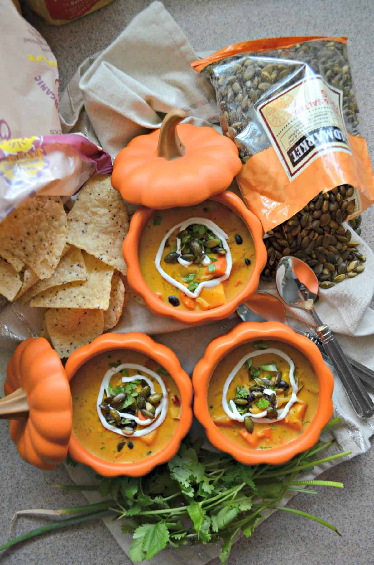 yellowish vegetable soup with white sauce on top in small pumpkin bowls next to tortilla chips and seeds.