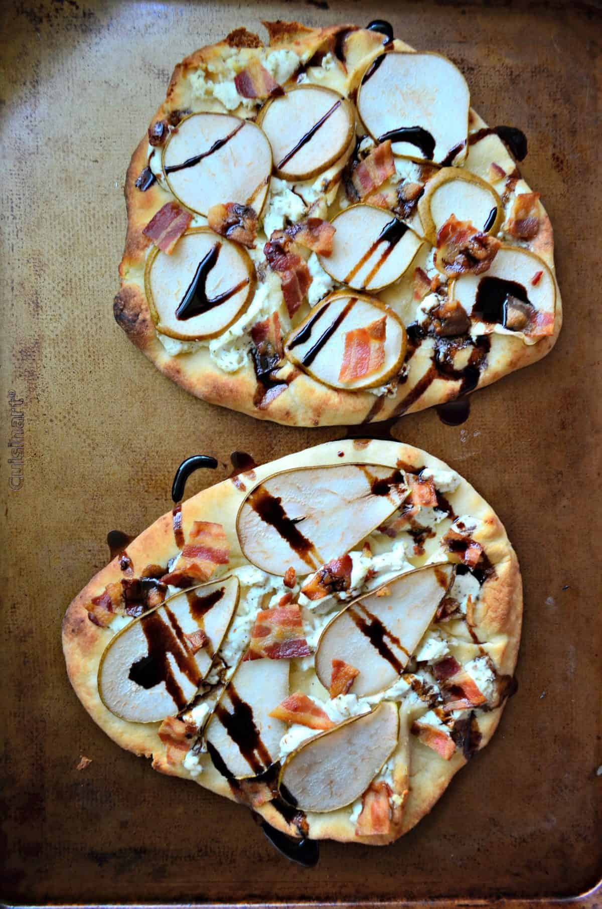 2 Goat Cheese, Bacon, and Pear Naan Flatbreads drizzled with brown sauce on light brown surface.