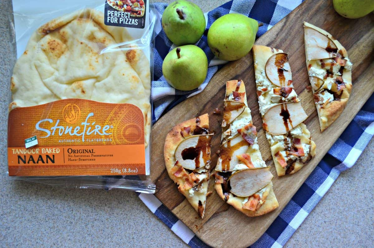 Goat Cheese, Bacon, and Pear slices on naan topped with brown sauce drizzled on board next to naan package.