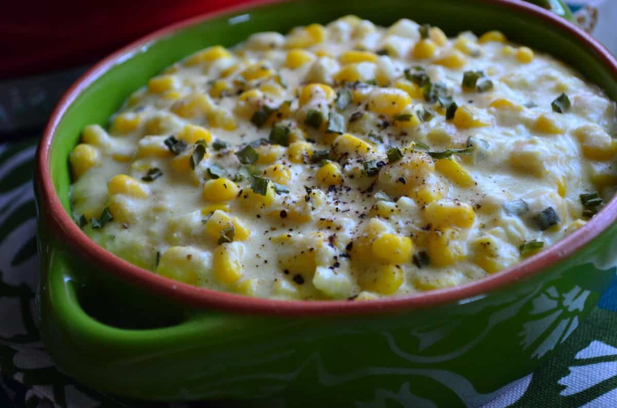 closeup of creamed corn topped with spices and herbs in green bowl.