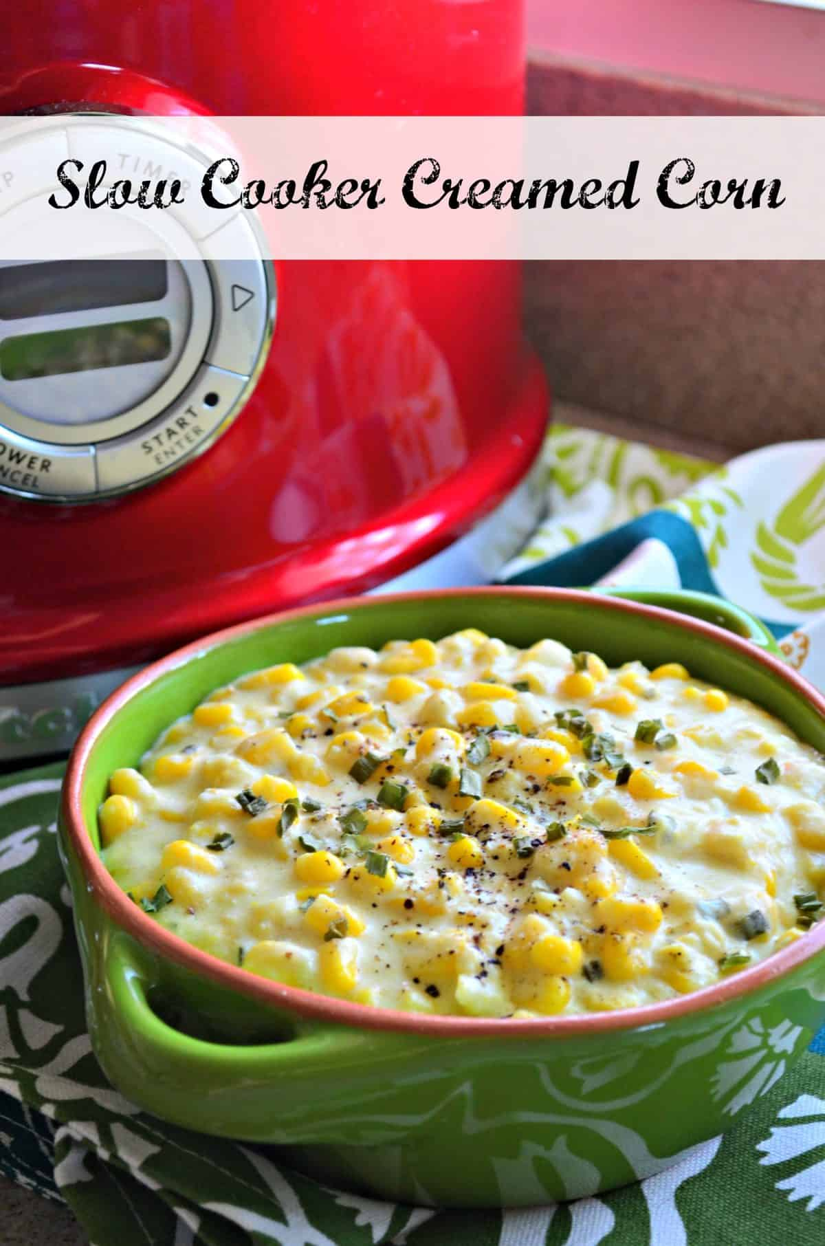creamed corn topped with spices and herbs in green bowl in front of red slow cooker with title text.