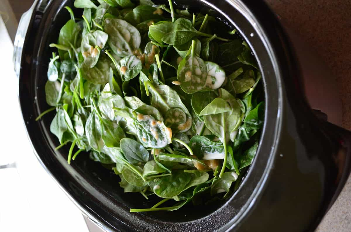 top view of baby spinach in slow cooker.