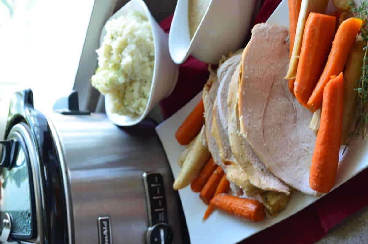 sliced Turkey with Carrots & Parsnips on rectangular white platter in front of gravy and mashed potatoes.