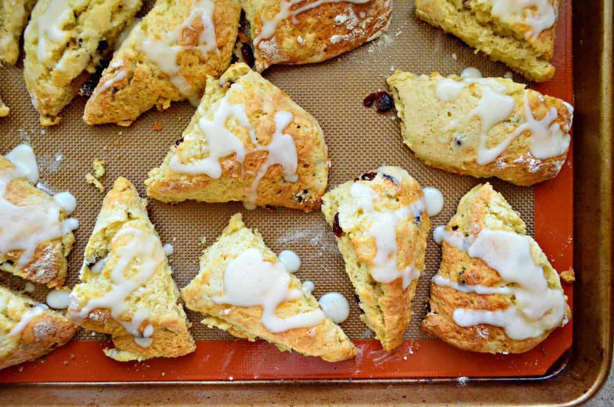 Top view of Cranberry Vanilla Yogurt Scones on baking sheet drizzled with white icing.