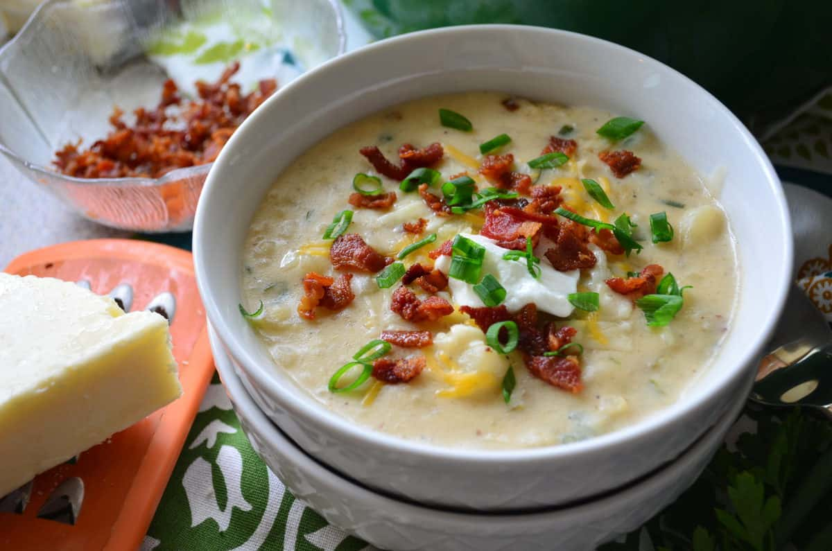 potato soup in white bowl topped with chives, bacon bits, cheese, and sour cream next to cheese and grater.