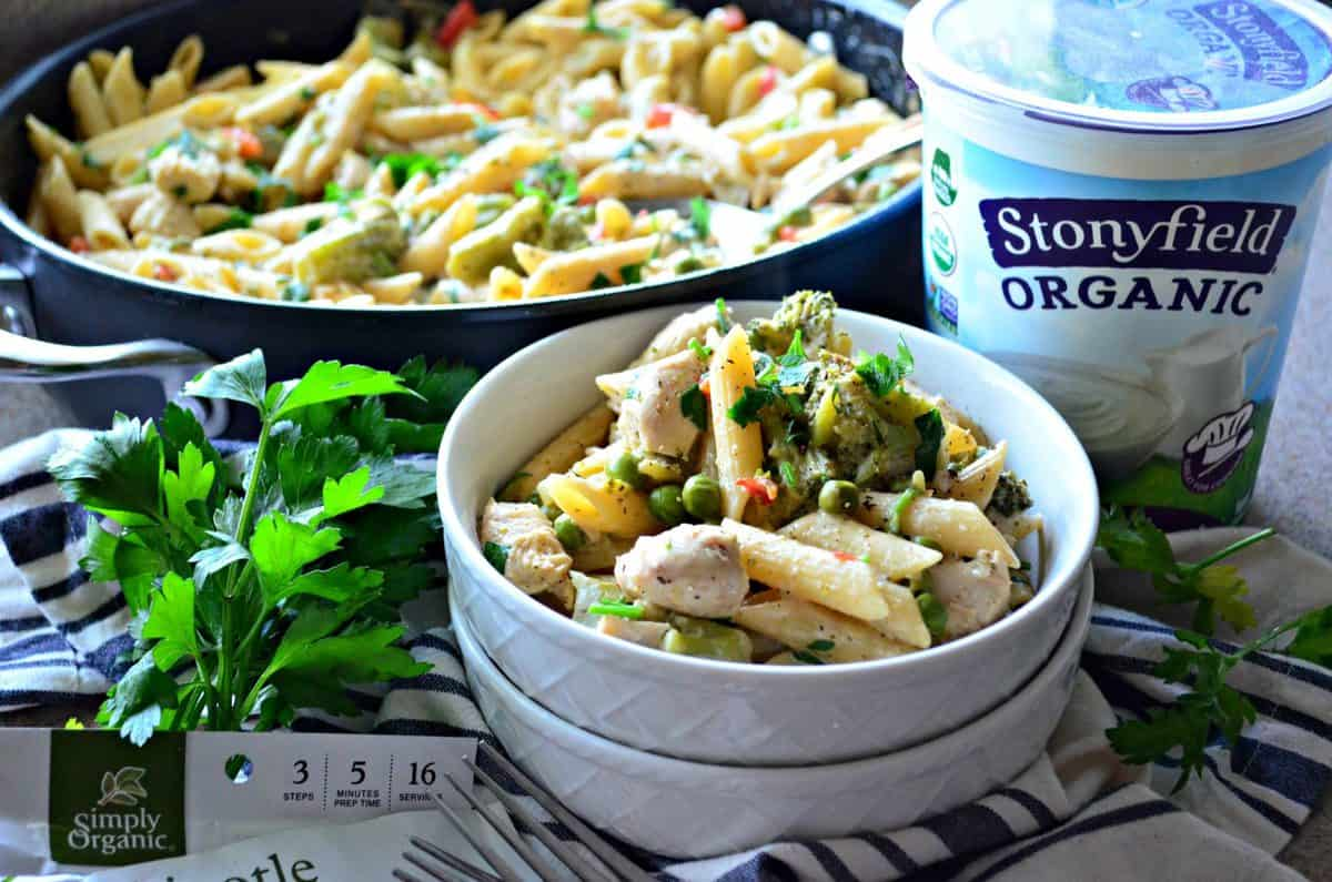 bowl and skillet of penne with peas, herbs and spices, bell peppers, and broccoli near yogurt and parsley.