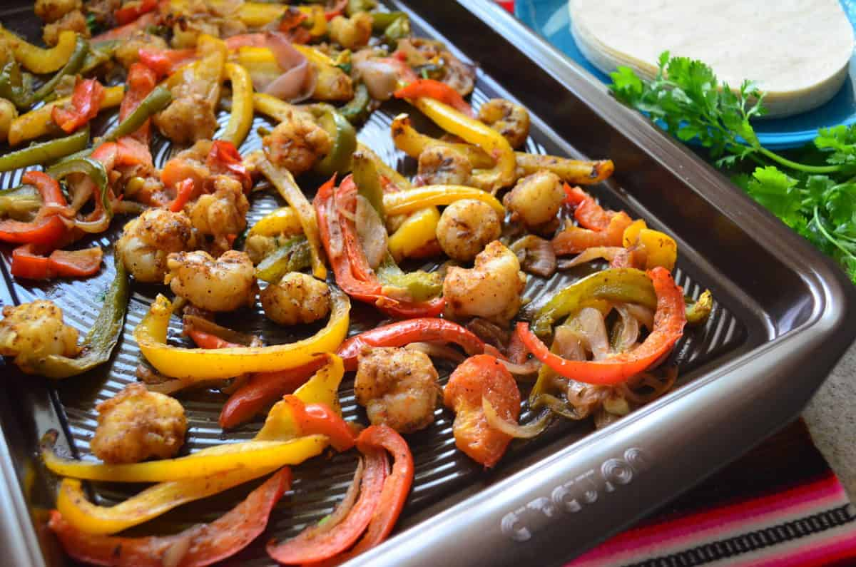 seasoned shrimp, sliced bell peppers, and onions on a sheet pan next to fresh cilantro and tortillas.