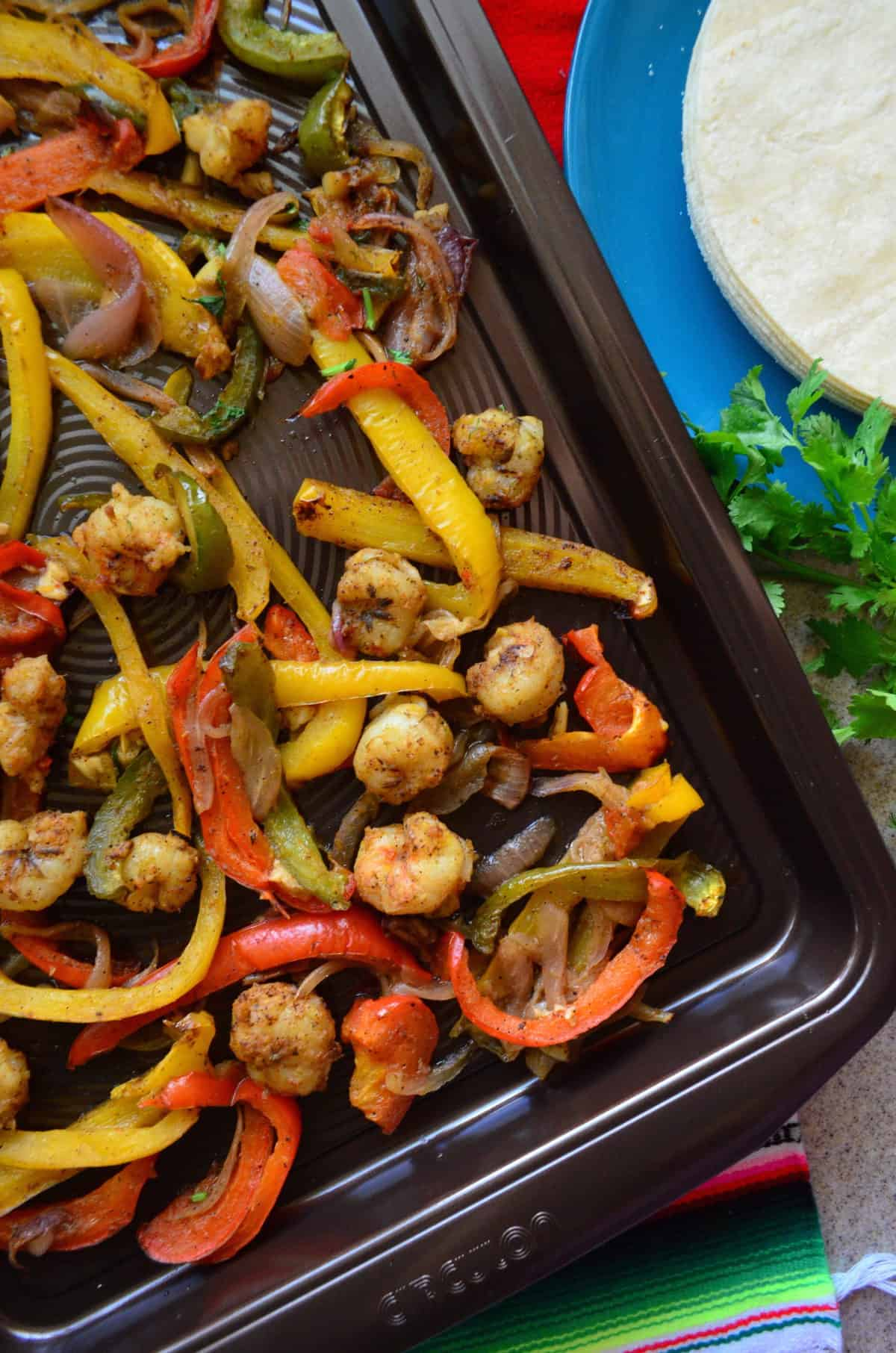 top view close up of seasoned shrimp, sliced bell peppers, and onions on a sheet pan.