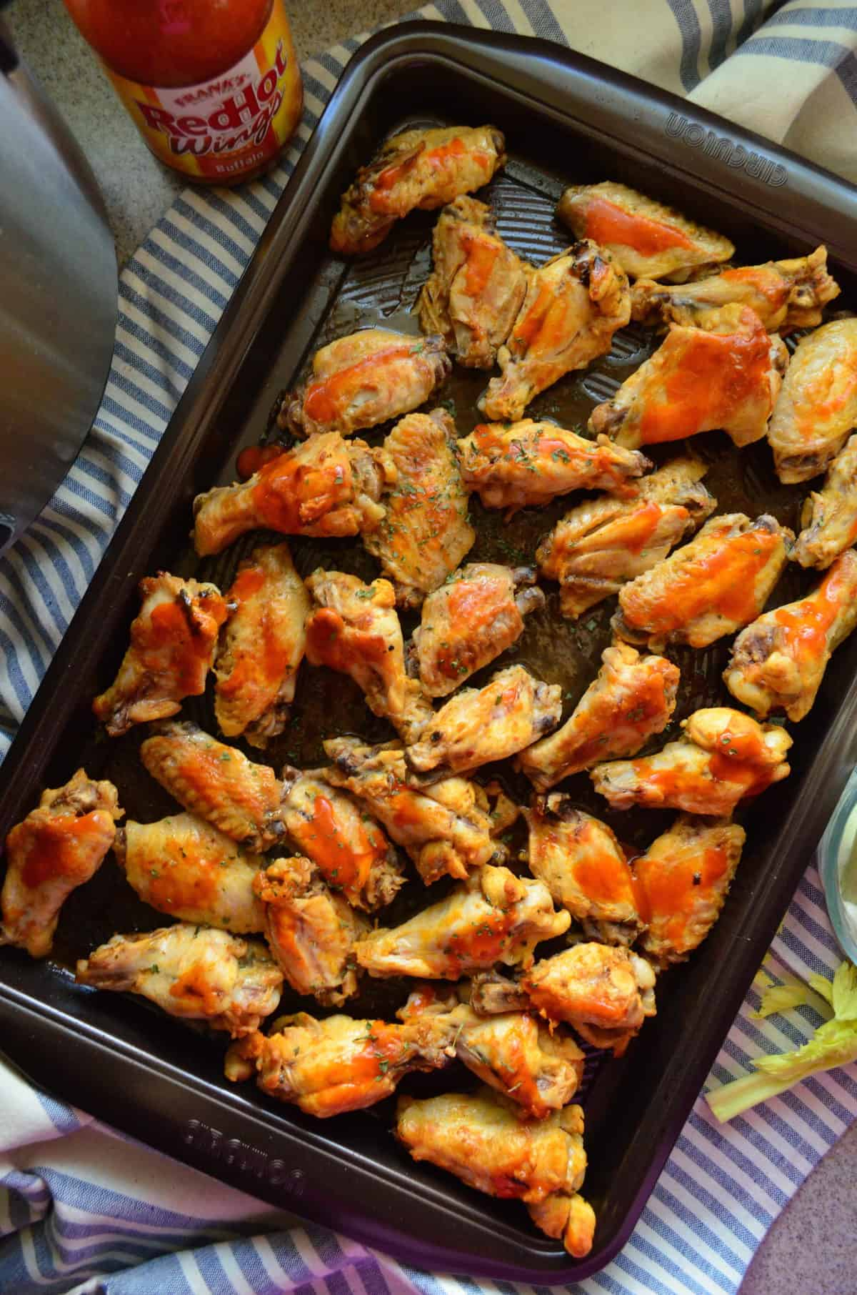 top view of wings smothered in buffalo sauce and spices on sheet pan.