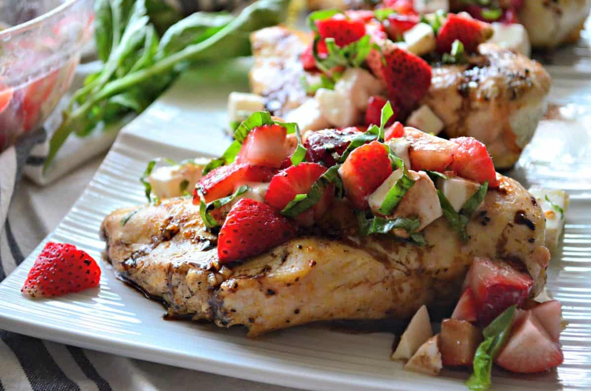 grilled chicken topped with basil, strawberries, and balsamic sauce on rectangular white platter.